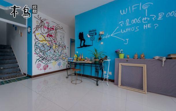 墙壁上手绘的漂流瓶和挂在麻绳上的手工五彩漂流瓶,一上一下仿佛票在